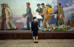 A train conductor stands in one of Pyongyang's lavish metro stations, in front of a Communist mural depicting happy workers Picture: Athanasiadis/Demotix
