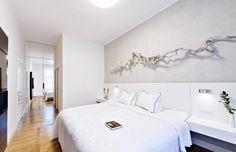 Stěna v záhlaví lůžka je ošetřena speciální stěrkou Oikos, která věrně imituje beton. Část nábytku v záhlaví lůžka je pro větší pohodlí čalouněna bílou koženkou