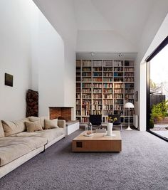 Openminded livingroom with high ceiling, large windows, light and a spacious feeling, and an amazing bookshelf.