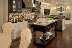 A galley-style kitchen and dining room were expanded to create this open concept kitchen. Fresh cream accents, a mosaic tile backsplash and a small brown island with a stainless steel top complete the stylish space.