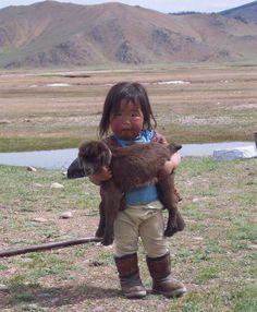 Criança pequena com carneirinho no colo