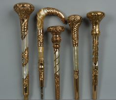 FIVE GOLD FILLED PARASOL HANDLES, 1890-1910 Four with mother of pearl and ball finial. One hook handle with caramel onyx. 7-10 inches. $287.50