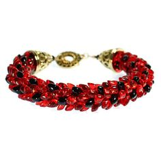 Everyone just loves kumihimo jewelry and this red and black beaded kumihimo bracelet is no exception. This medium wrist bracelet is made using ruby red and shiny black Japanese magatama beads. In the pattern called pinecone or dragon scales. I think it looks like ladybug jewelry, just perfect for the lover of all things ladybug. These quality beads are braided using 8 strong ruby red nylon cords in the ancient Japanese kumihimo technique. Key Features: * fits a medium 6.0 to 6.75 inch wrist…