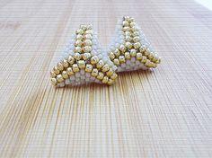 Náušnice zošité z korálok zlatej a krémovej farby.