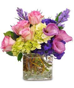 Calla lilies in a bright pink hue are accented with green hydrangea and lovely pink roses. Touches of purple blooms complete this any occasion arrangement! #citylineflorist #hydrangea