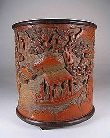 "Carved Chinese Scholar's Bamboo Brushpot, Qing SCH383  DESCRIPTION: A very good Chinese scholar's brushpot, carved in deep relief with a continuous mountain landscape scene framed by gnarled pine trees and depicting scholars examining a scroll and in a boat. The base and rim are encased in hardwood and the pot is engraved with a two line inscription. Very good condition, Qing Dynasty, 19th C. DIMENSIONS: 6 1/2"" 1150."