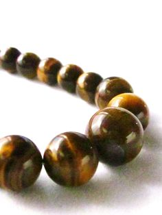 """Natural Tigereye Stone Necklace. Most Tigereye comes from South Africa. This beautiful, warm, glowing brown stone is said to inspire positive energy on even the gloomiest of days.    19"""", with gold plated barrel clasp. $25"""