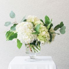 Classic Hydrangea Centerpiece in Glass Compote — fleurs petite is part of Hydrangea arrangements wedding - An all white hydrangea arrangement for a New England wedding will never go out of style White Hydrangea Centerpieces, White Flower Arrangements, Wedding Table Centerpieces, Centerpiece Ideas, Hydrangea Wedding Arrangements, Hydrangea Wedding Decor, White Hydrangea Bouquet, Wedding Decorations, Centerpiece Flowers