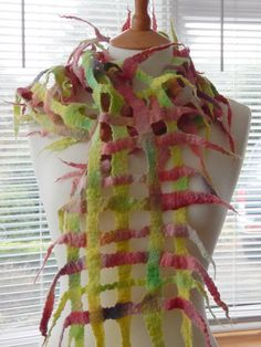 This beautiful lattice scarf is hand-made from 100% Merino wool, which is hand-dyed by Shunklies UK in shades of pastel pinks, yellows and greens. The scarf is wet felted by hand in one piece, a process that takes many hours. The dry fibres are laid out in the lattice formation, then carefully soaked in warm soapy water and gently rubbed by hand until the felting process is complete. The criss-crossing of the fibres forms a lattice shape with wonderful organic tendrils which frame the face…