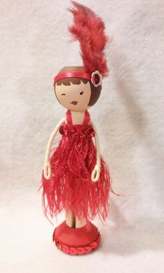 SugarlandDollHouse-Flapper Girl Miniature Wooden Clothespin Doll wooden clothespin doll stands just over four inches tall (a little over six with the feather), and is uniquely hand painted, wearing a red fringe dress with sequined embellishments