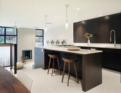 """Non-kitchen, kitchen: To keep the open space from screaming 'kitchen,' we avoided upper cabinets,"""" says Sherman. Instead, the storage is hidden behind full-height white lacquered panels. At the sink wall, the thin stainless steel line that separates the flush anigre panels from the Ceaserstone backsplash is a recessed plug strip."""