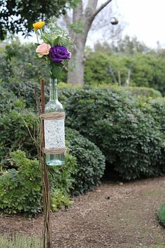 wine bottles covered in lace tied with jute and raffia to line the wedding aisle