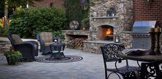 Relaxing patio area featuring an outdoor fireplace, grill, seating area, and dining area. #DublinPaver