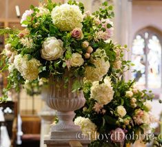 Summer flowers, peonies, roses and hydrangea in stone urn