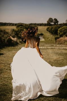 This sleeveless gown features a plunging v-neckline that leads to an airy A-line skirt gently gathered at the waist; covered buttons accent the illusion back. Photo: @chadmunrophoto
