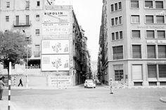 1966 girona Encreuament del Carrer Nou amb la Gran Via Jaume I. A la dreta el Banco Vitalicio. Al mur de l'edifici de l'esquerra s'observen diferents falques publicitàries de pintures i begudes. A l'encreuament del carrer hi ha un Policia Municipal dirigint el trànsit