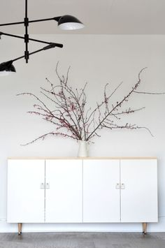 "DIY MODERN WHITE AND NATURAL WOOD BUFFET  This was so quick and easy!   Grab two 36"" Ikea cabinets, some tapered wood legs, a wood top, leather and brass bolts for handles, and you're good to go.  Enormous branches optional."