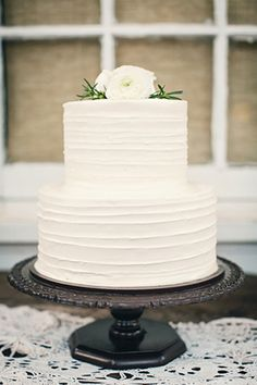 all white buttercream wedding cake on vintage stand