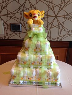 Square Diaper Cake Top tier 1 row of 5 diapers 2nd tier 2 rows of 10=20 diapers 3rd tier 3 rows of 15=45 diapers Bottom tier 4 rows of 20=80 diapers 150 total size 2 Pampers Swaddlers 16 inch square cake base 2 Dow rods down center of cake White curling ribbon to tie diapers in rows.  10 yd of sheer green 1 1/2 in ribbon 4 yd of safari animal 1 1/2 in ribbon Baby Simba for top Baby Shower Items, Baby Shower Diapers, Baby Shower Gifts, Baby Gifts, Baby Simba, Lion King Baby Shower, Baby Boy Shower, Diaper Cakes Tutorial, Lion King Party