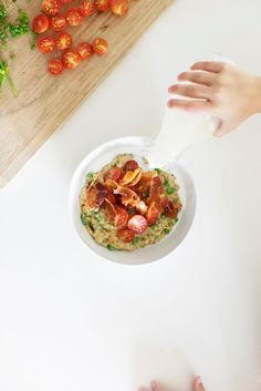 Night Cereal: Savory Cheddar Oats created by Mother Mag || 1/2 cup whole milk, 1/4 cup water, 1 1/2 cups chicken stock, 1/2 cup steel-cut oats, 1/2 cup cheddar cheese, 1/4 cup fresh chives, chopped 6-8 slices pancetta, 1 cup grape or cherry tomatoes, halved 1/2 cup frozen peas, Salt and pepper to taste