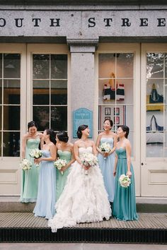 Bride with bridesmaids wearing different coloured blue dresses