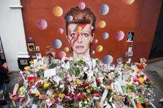 Nachdem bekannt geworden ist, dass Pop-Star David Bowie im Alter von 69 Jahren an den Folgen einer Krebserkrankung gestorben ist, gedenken weltweit tausende von Fans dem genialen Musiker. Vor einem Gemälde des australischen Streetart-Künstlers Jimmy C legen Trauernde in London Blumen nieder.
