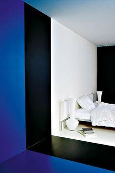 De la couleur pour délimiter l'espace Dans sa maison qui ne possède aucune cloison, l'architecte Luc Binst emploie la couleur dans le but de délimiter les espaces. Ainsi, la chambre blanche donne sur la salle de bains habillée de bleu. Pour séparer les deux pièces l'architecte a choisi de peindre une large bande noire comme un mur imaginaire.