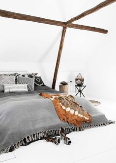 Boho inspired bedroom with a gray bedding and exposed wooden beams
