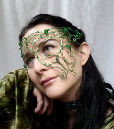 Gorgeous plant themed ladies half mask. In green enamelled wire with hand beaded leaves, sweeps down from the band to cover one cheek. Has