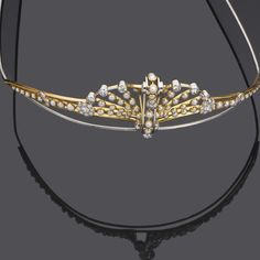 A gold, diamond and half-pearl tiara, made in 1935 for a Court Presentation in 1938 of a young lady. Then by descent until sold by Bonhams on 19th September 2007 for £3,840. A classic art deco fan motif.