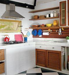 Portas do tipo veneziano mantêm o interior dos armários sempre arejados. Para guardar mantimentos e utensílios, cestos de fibra natural são bons substitutos das gavetas.