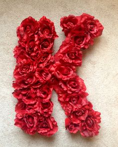 Red Rose K to hang on the wall. Spray painted a large wood K, drilled holes to accommodate the buds, then hot glued 24 roses.  Red Nursery Baby Room