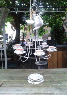 kandelaar met theekopjes en theepot met eigengemaakte kaarsen