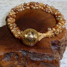Kumihimo Seed Beaded Bracelet with Shades of Gold and Amber in Metallic and Frost with Gold Button Closure on Etsy, $23.00
