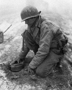 Mining a road, a combat engineer lowers a 10-pound antitank charge into a hole and prepares to scoop dirt over it. Sometimes two mines were buried together to increase chances of disabling a heavily armored Tiger tank (Battle of the Bulge, Dec. 1944).