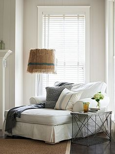 A crab trap side table and a lamp bookend this living room's Shabby Chic chaise lounge.