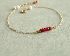 This feminine small ruby bracelet has genuine Longido red rubies, small beads (real gemstones and the stone for July birthdays) at its center, surrounded by a simple 14K goldfilled chain which leads to freshwater white natural pearls at the back. The clasp is a 14K goldfilled spring clasp, and theres an additional small ruby hanging from the closure chain.  The bracelet is petite and graceful, yet very striking. The red rubies are faceted, opaque, and a rich pink red ruby color, perhaps a…
