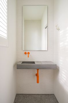 Simple, minimal bathroom design by Martha's Vineyard Interior Design featuring a striking combination of our Flor Mini concrete basin with bright orange tapware by vola.