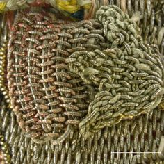 Floral and insect motifs are overlaid with detached needle lace details in gold and silver filé, gold spangles, and coiled wire.  Magnification 10x. Image by Cristina Balloffet Carr. early 17th century, British. Canvas worked with silk and metal thread, glass beads, spangles; Gobelin, tent, and detached buttonhole stitches; silk cord and silk and metal thread tassels. 5 1/8 x 5 1/8 in. (13 x 13 cm), excluding tassels and draw cord. Rogers Fund, by exchange, (29.23.15)