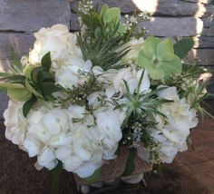 Arrangement in greens and whites.  White hydrangea, green thistle, helleborus and wax flower in a burlap detailed glass cube.