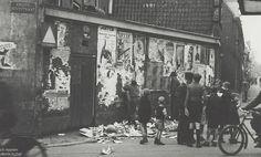 De gehate aanplakbiljetten van de Duitsers en de NSB worden verwijderd van het reclame-muurtje op de hoek van de Doelstraat en de Grote Houtstraat, 5 mei 1945