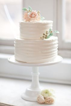 White, 2-tiered cake with pink gum paste flowers and gold berries with mint leaves
