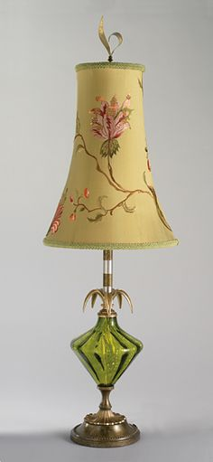 Created by Caryn Kinzig and Susan Kinzig  Richness and tranquility shine in blown glass. This table lamp features a round shade made from dupioni silk and embroidered with a floral design. Solid brass base with a striped stem of patinated brass and aluminum, and blown glass elements.