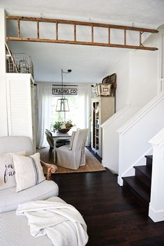 Using an antique ladder as a faux wooden beam - It adds a visual separation of two rooms