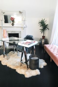 Feminine minimalist office decor | chic West Elm glass desk on a white fur rug, Wayfair pink tufted bench, black wood floors and bright white walls | Office of graphic designer, Candace Ross | @StudioMeroe | www.studiomeroe.com
