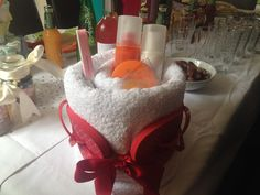 Pamper 'cake' kit - white rolled towel cake, filled with body lotions, shower gel, nil varnish and flip flops attached on the outside - all in one colour scheme. Perfect for a mum to be