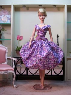 "Bubble Dress in Liberty of London ""Saeed""This beautiful print from the 2015 Liberty collection is an eclectic mixture of hand drawn photo realistic pansies and abstract violas in shades of purple.The off the shoulder, dropped waist bodice has a ruched bodice embroidered with tiny purple beads.A silk bow belt in dusky amethyst defines the waistThe voluminous bubble skirt is as airy and light as a souffle."