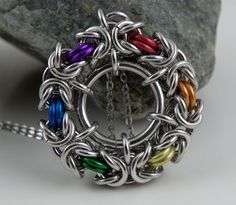 This fun rainbow chainmaille pendant always catches attention.    This pendant was created around a centre ring that stabilizes the byzantine