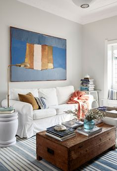 White couch and colourful accents in living room of heritage Sydney family home.
