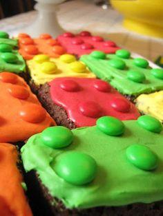 Lego Brownies: Benodigdheden: ⦁ 1 brownie, zelfgemaakt of kant-en-klaar  ⦁ 200 gr poedersuiker  ⦁ water  ⦁ kleurstoffen in de kleuren van de m&m's of smarties ⦁ m&m's of smarties Bereidingswijze: Maak de brownie volgens de bereidingswijze en laat deze helemaal afkoelen. Bereid ondertussen het glazuur. Verdeel het glazuur over bijvoorbeeld 3 of 4 bakjes. Voeg in ieder bakje een ander kleurstof toe. Besmeer de brownies met het glazuur en leg de m&m's, met het logo naar beneden.